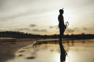 Silhouette of  spear fisherman in shallow water at sunset