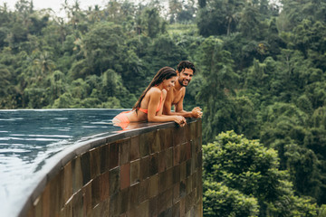Happy young couple standing at edge of swimming pool