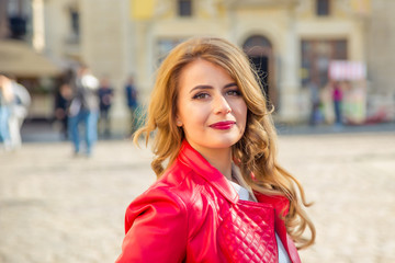 happy woman in a red jacket on sunny day