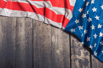 An American Flag Lying on an aged, weathered rustic wooden background
