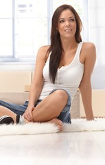 Pretty woman sitting on floor at home smiling