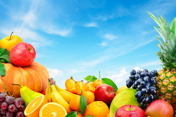 Large collection of fruits and vegetables on a blue sky background