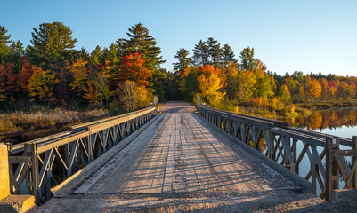 Early October, late afternoon sunshine on a portable deploy-able, single lane, steel and timber bridge over Cory Lake in Chalk River Ontario, Canada.