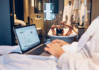 Couple in top level hotel: man working using laptop,female bathi