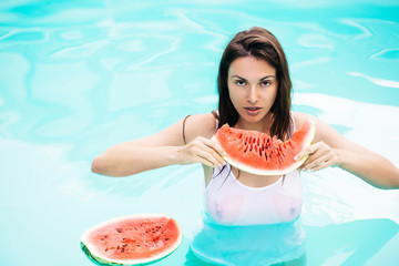 brunette with watermelon in pool
