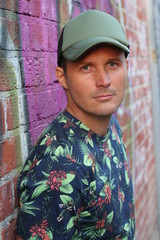 Caucasian American Man Casual Street Fashion in New York, wearing blue flower patterned shirt, green cap, standing by graffiti wall, seductive look