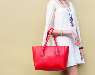 Fashionable beautiful big red handbag on the arm of the girl in a fashionable white dress, posing near the wall on a warm summer night. Warm color. Close up