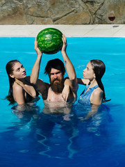 women and man with watermelon in swimming pool