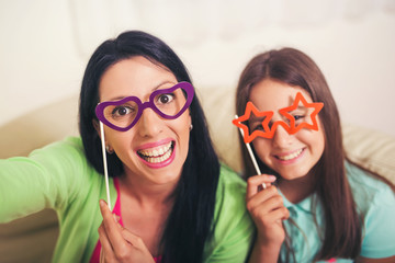 Mother taking selfie with daughter holding artificial mustache
