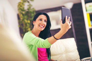 Portrait of a beautiful woman taking a selfie with her digital tablet