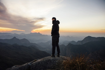 Man looking away while standing on mountain during sunset