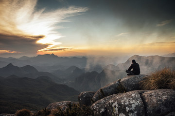 Rear view of man sitting on mountain rock during sunset