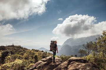 Side view of male backpacker standing on mountain against cloudy sky