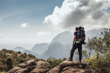 Male backpacker standing on mountain against sky