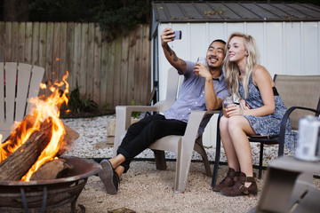 Friends taking selfie while sitting on chairs at yard