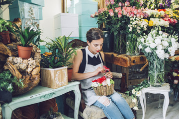 Florist arranging flowers in pot at store