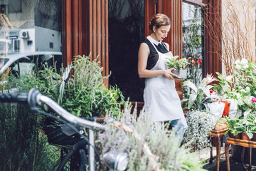 Florist carrying potted plant while standing at entrance of shop