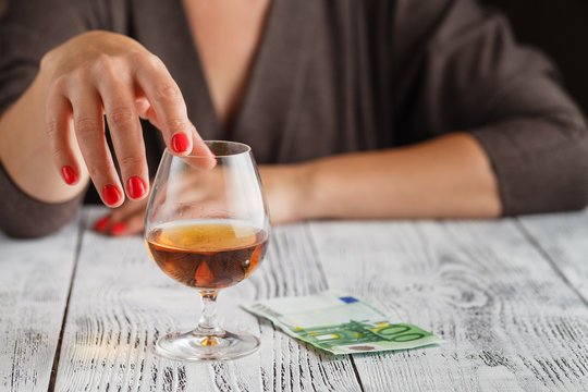 A woman's hand is touching a glass of cognac
