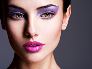 Spoed Fotobehang Beauty Beautiful girl's face closeup with purple eye make-up. fashion m