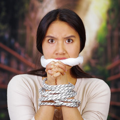 Young brunette woman wearing white sweater tied up with rope around wrists and covering mouth, facing camera, hostage concept