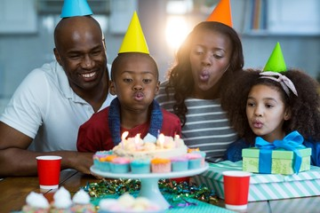Family blowing out candles on birthday cake