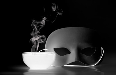 Smoke rising from a glowing bowl with mask