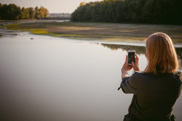 pretty blonde girl in sneakers, nylon stockings and coat. walks and photographed on a smartphone selfi on the stone shore of the lake in the last sunshine of the departing summer.