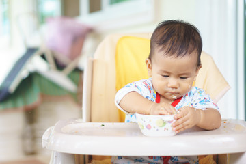 Asian baby eating food by himself