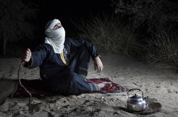 Tuareg man in a desert, making tea