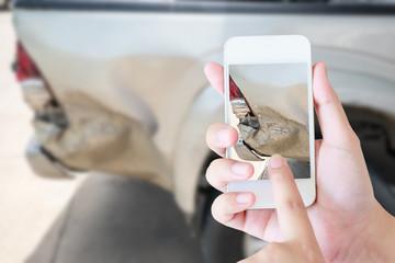 woman using smart phone to take car damage photo