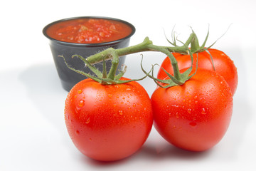 Three tomatoes and a cup of salsa.