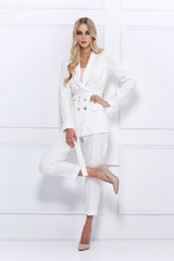 High fashion shot of young woman in white suit