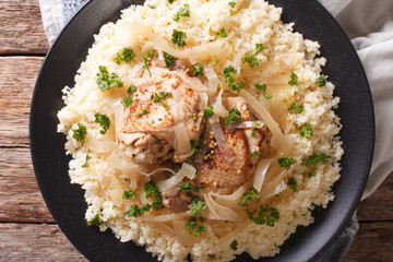 Senegalese cuisine: chicken Yassa with couscous and onions close-up. Horizontal top view