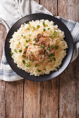 Yassa chicken with onions and garnished with couscous closeup. Vertical top view
