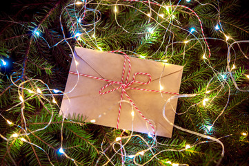 The letter in the envelope, a bright garland.spruce branches on a wooden background New year, Christmas