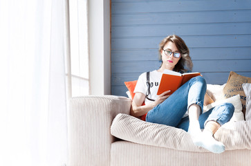 Young smart female student in round glasses studying at home near large window. Balcony, sofa, soft pillows. Orange textbook. Her hair is blue, she is dressed in jeans and a white T-shirt.