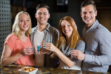 Group of friends standing at bar counter