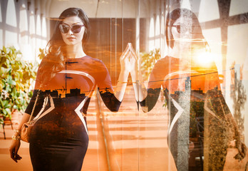 Double exposure of elegant woman with reflection and cityscape sunset