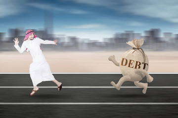 Middle eastern person running away from debt