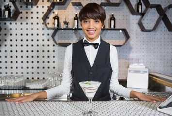 Waitress standing in bar counter with glass of cocktail