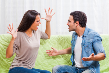 Young couple is arguing at home. They are yelling at each other.