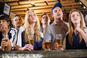 Upset fan watching football at bar counter