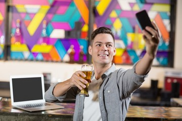 Young man taking a selfie while having a glass of beer