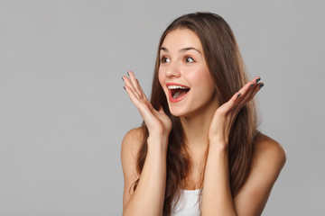 Surprised happy woman looking sideways in excitement. Isolated on gray background