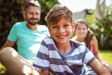 Smiling boy sitting in garden with father and sister