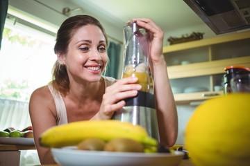 Smiling woman preparing smoothie