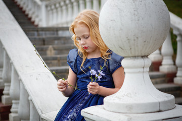 Portrait of beautiful little girl in the Park on the stairs