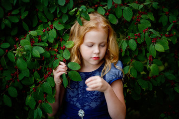 Portrait of beautiful little girl in a blue dress on a background of leaves cherries