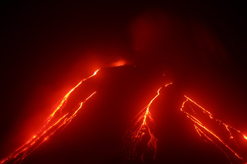 Volcanic landscape of Kamchatka: night view of eruption Klyuchevskaya Sopka, current lava flows on the slope of the volcano. Russian Far East, Kamchatka Region, Klyuchevskaya Group of Volcanoes.