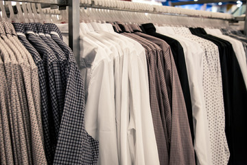 Men shirt in different style hang side by side on the rack in the store.